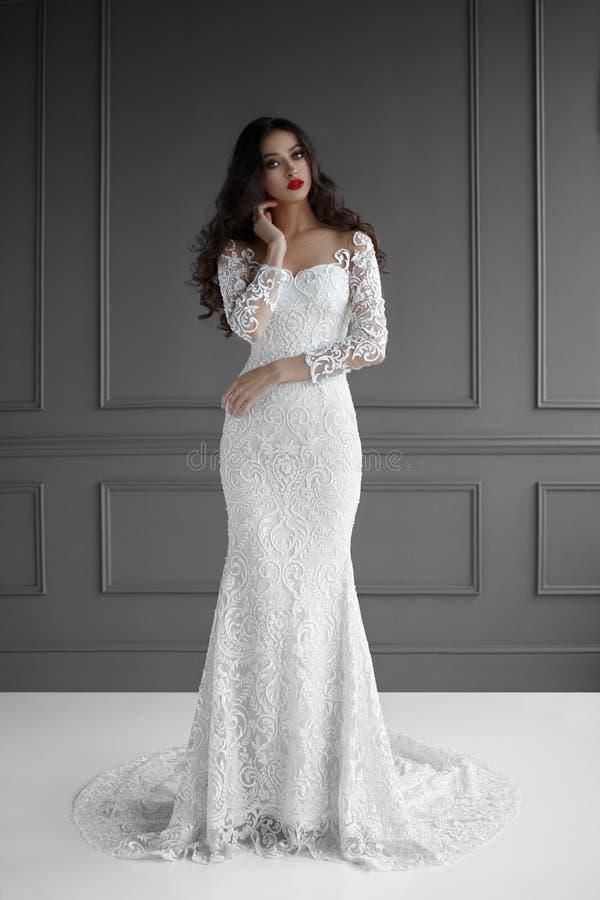 Женская модель с вьющиеся волосы в белом платье свадьбы, он касается его шеи с его рукой, на серой предпосылке стоковые изображения