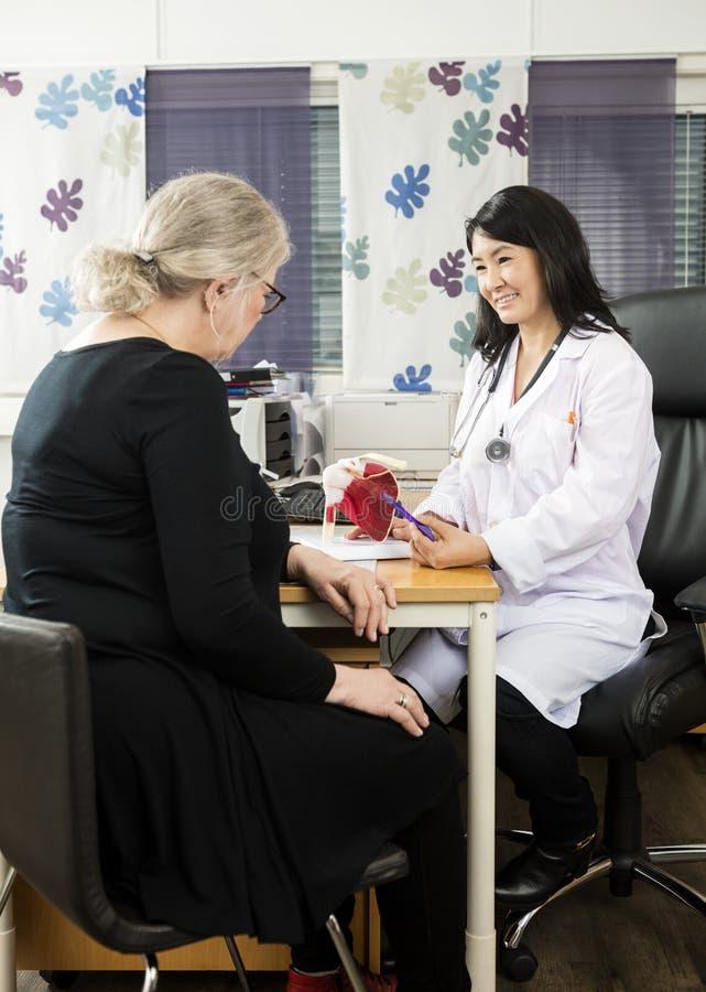 Женская модель тумака вращателя доктора Explaining к старшему пациенту стоковая фотография rf
