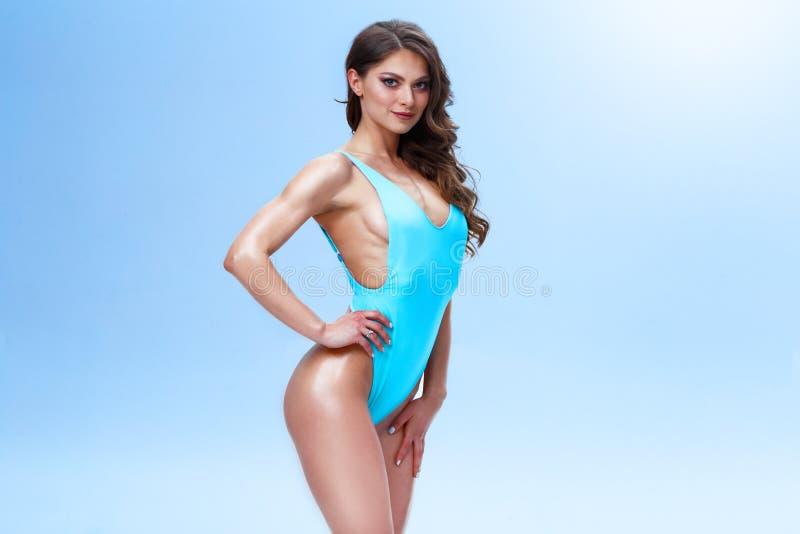 Женская модель фитнеса с sporty телом и длинными волосами представляет в светлой студии Фото сделано в красочном и стоковое фото