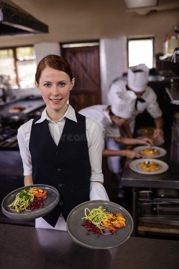 Женская официантка держа плиты с едой в кухне стоковая фотография rf