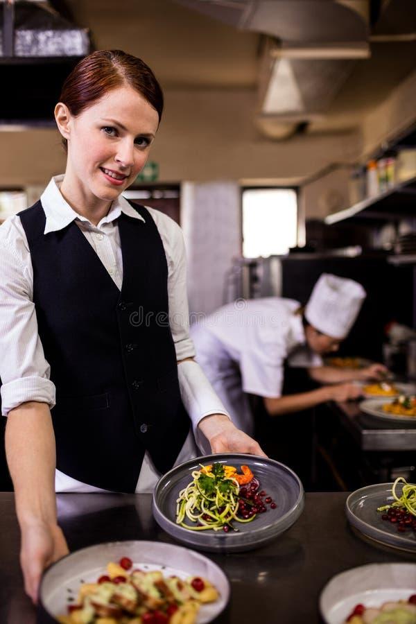 Женская официантка держа плиты с едой в кухне стоковые фотографии rf