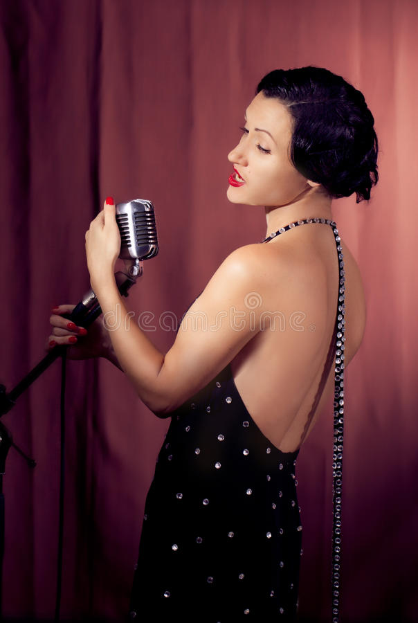 Женская певица с ретро микрофоном стоковые фото