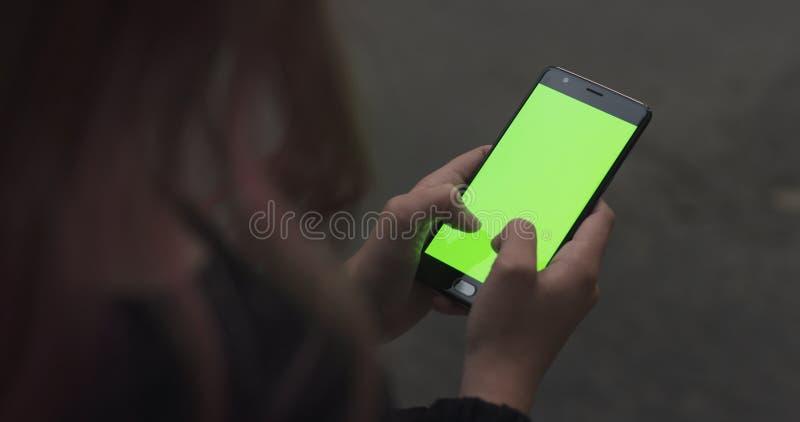 Женская предназначенная для подростков девушка используя smartphone при зеленый экран сидя outdoors стоковое фото