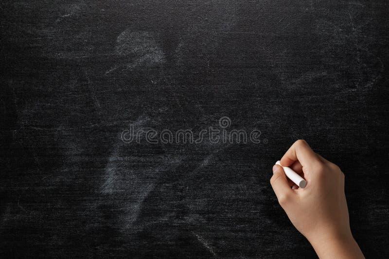 Женская предназначенная для подростков рука для того чтобы нарисовать что-то на классн классном стоковые фотографии rf