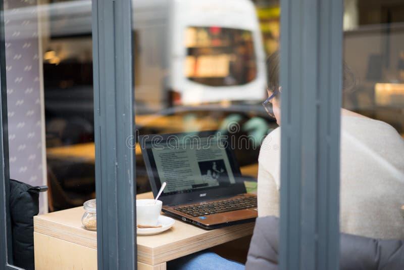 Женская работа на компьтер-книжке в кафе рука девушки используя компьтер-книжку в магазине coffe стоковые фотографии rf