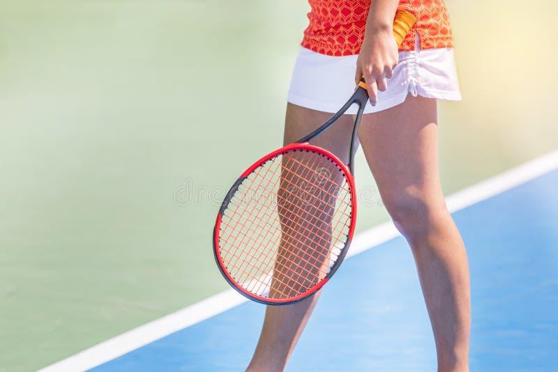 Женская ракетка удерживания теннисиста подготавливая для игры в теннисном корте стоковые фото