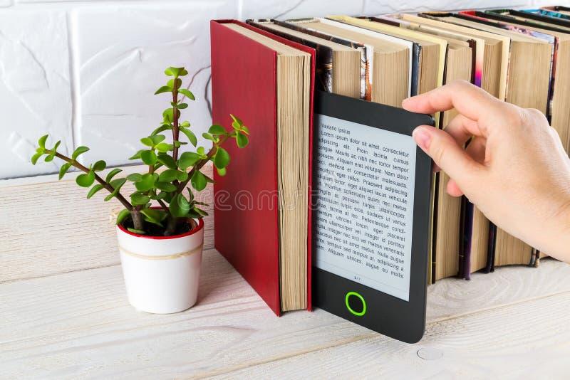 Женская рука берет с полки электронно-читателя бумажные книги и маленькое горшочечное растение Копирование места на экране электр стоковые изображения rf