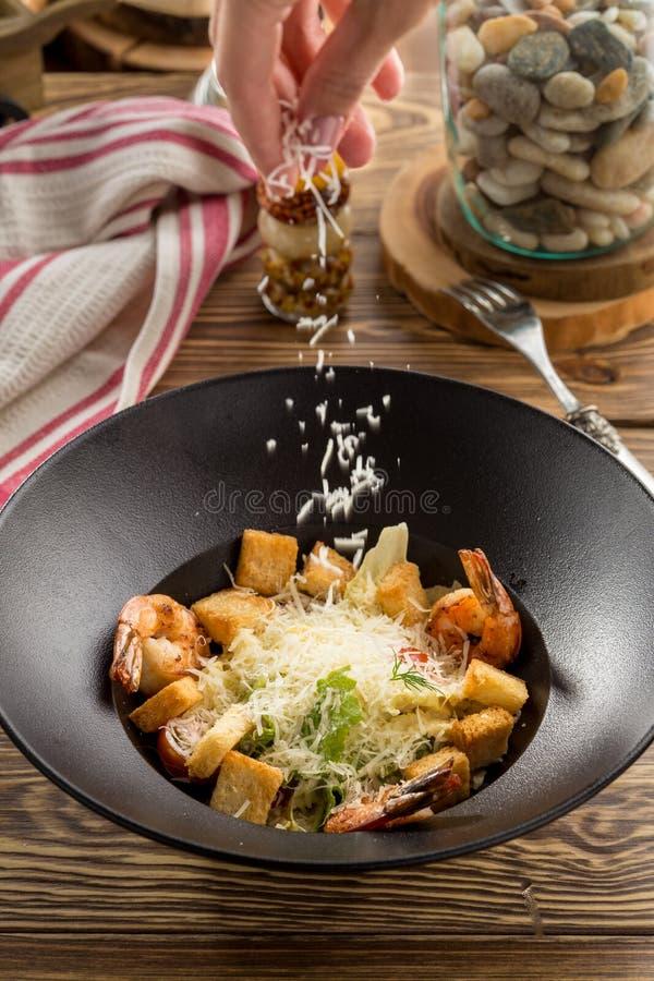 Женская рука брызгая заскрежетала сыр пармезан на салате свежего овоща с креветкой и гренками стоковое изображение
