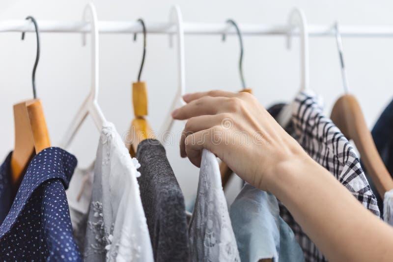Женская рука выбирает одежды на вешалке стоковые фотографии rf