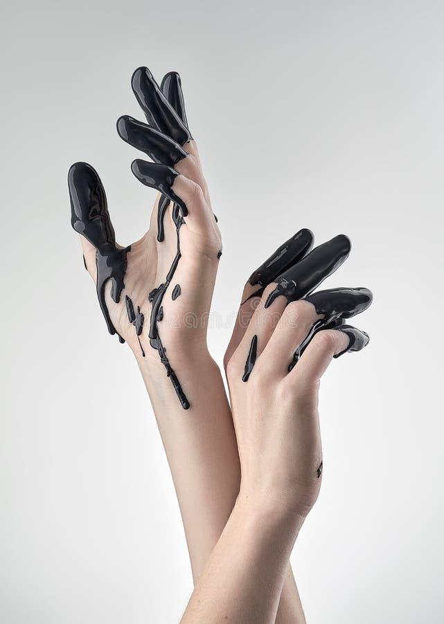 Женская рука в черном смазочном минеральном масле стоковые фото