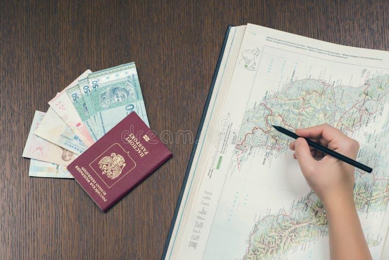 Женская рука делая знак на карте Малайзии для планировать отключение Русский биометрический пасспорт, малайзийские деньги на пред стоковое фото
