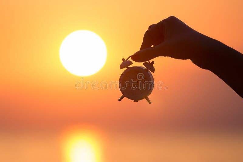 Женская рука держа будильник на восходе солнца стоковые фото