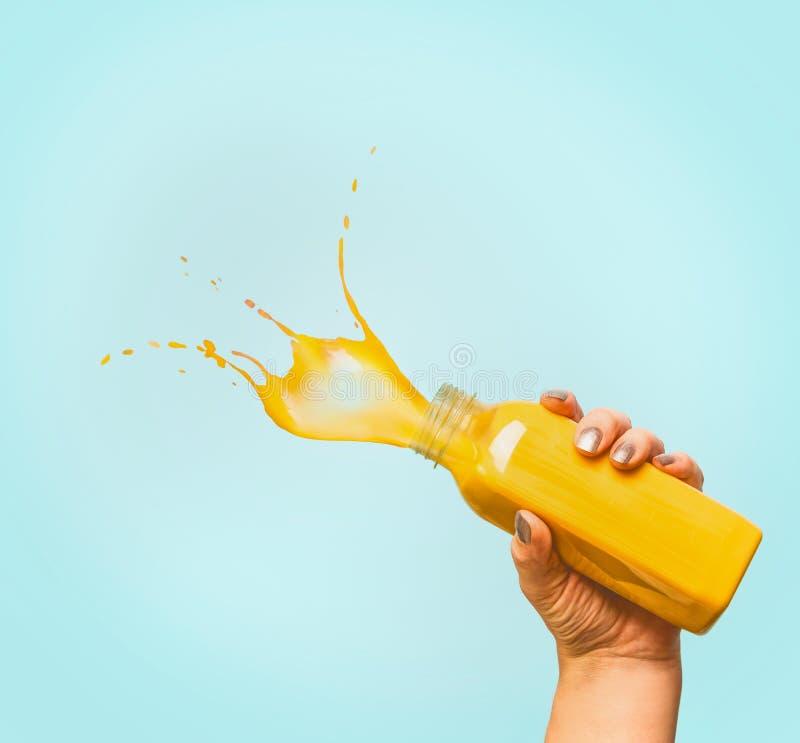Женская рука держа бутылку с желтым напитком лета выплеска: smoothie или сок на сини стоковая фотография rf