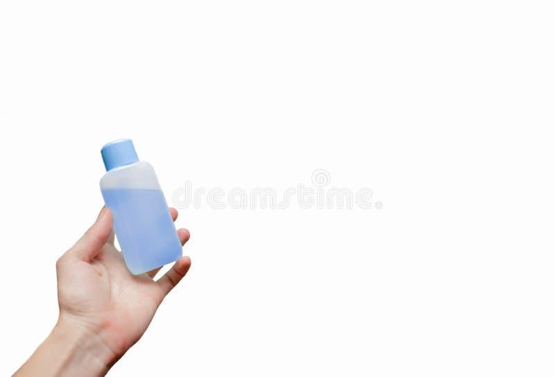 Женская рука держа бутылку с стоковые изображения