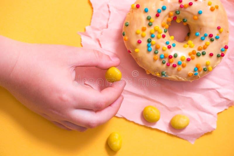 Женская рука держа донут с брызгает на желтой предпосылке стоковое изображение