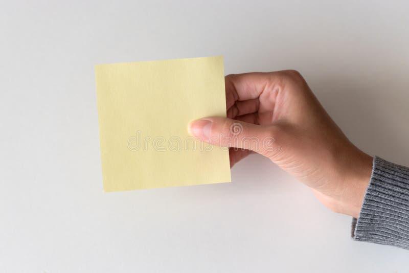 Женская рука держа карточку чистого листа бумаги стоковое изображение