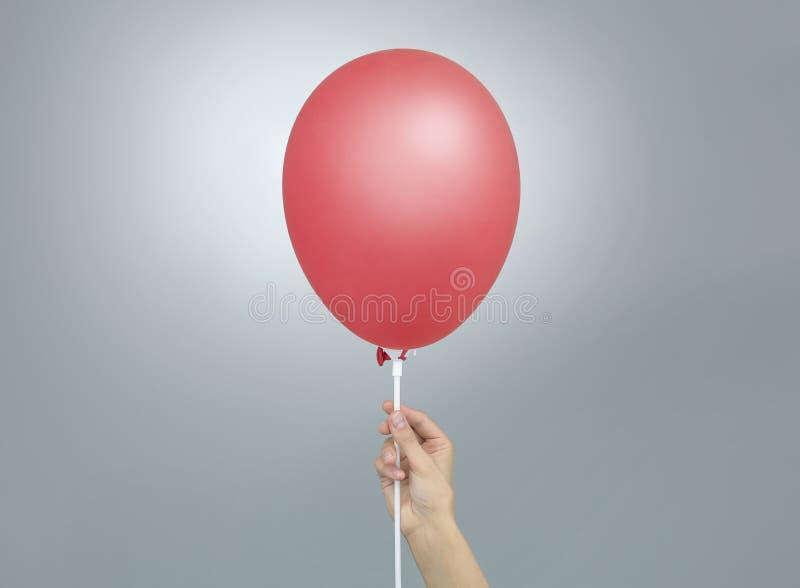 Женская рука держа красный воздушный шар стоковое фото rf