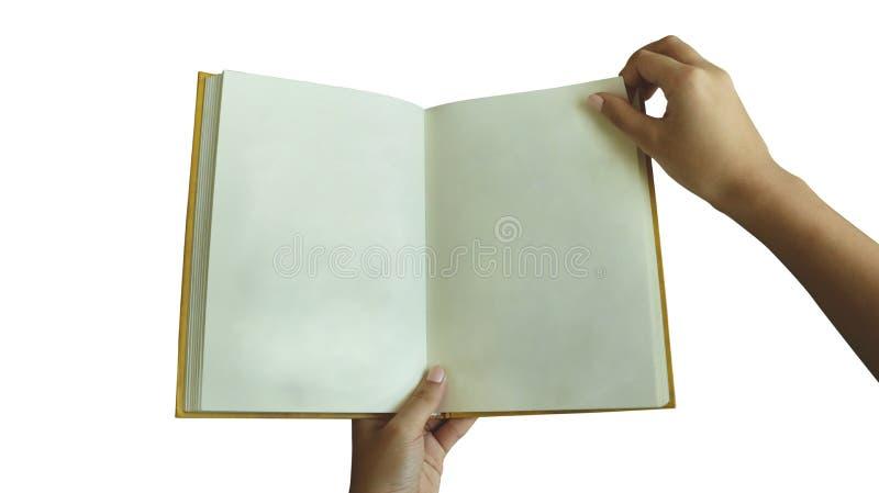 Женская рука держа пустую книгу слегка ударяя страницу на белой предпосылке - реальном винтажном бумажном Hardback желтого цвета  стоковая фотография rf