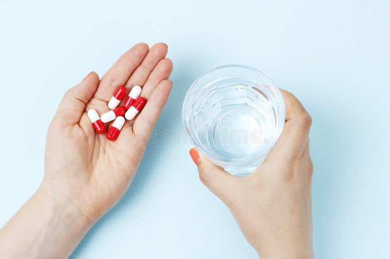Женская рука держа стекло воды и таблеток, взгляда сверху стоковое изображение rf