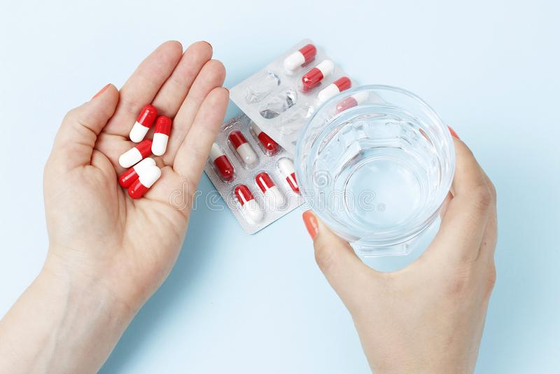 Женская рука держа стекло воды и таблеток, взгляда сверху стоковые фото