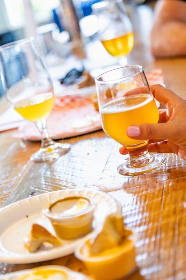Женская рука держа стекло микро- пива brew на баре стоковые изображения