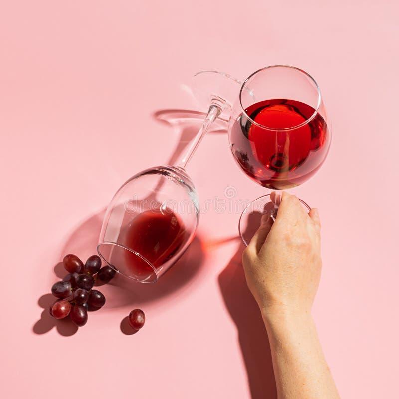 Женская рука держа стекло с красным вином и связкой винограда на нежной розовой предпосылке r minimalism стоковое изображение rf
