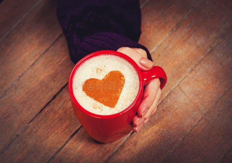 Женская рука держа чашку капучино с циннамоном формы сердца стоковая фотография rf