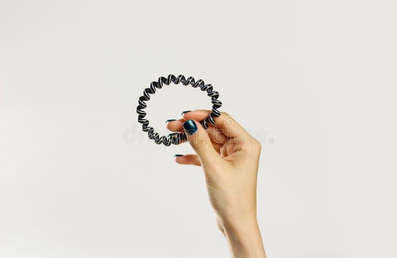 Женская рука держа scrunchie пластмассы спирально Изолировано на сером цвете стоковые фото