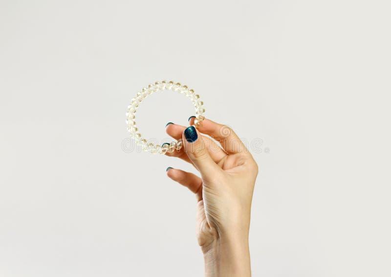 Женская рука держа scrunchie пластмассы спирально Изолировано на сером цвете стоковое изображение rf