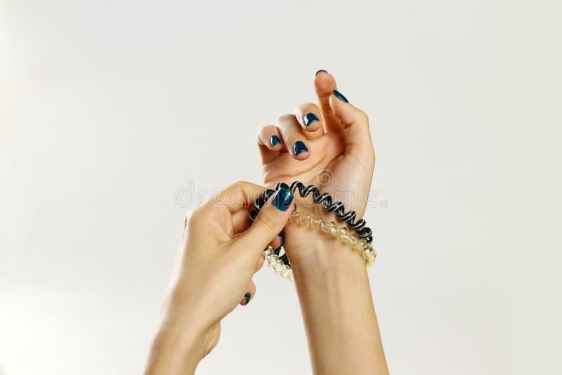 Женская рука держа scrunchie пластмассы спирально Изолировано на сером цвете стоковые изображения