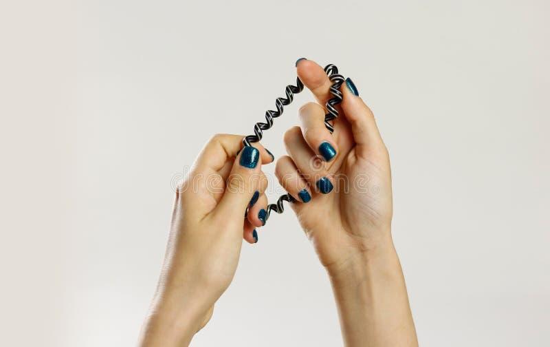 Женская рука держа scrunchie пластмассы спирально Изолировано на сером цвете стоковые изображения rf