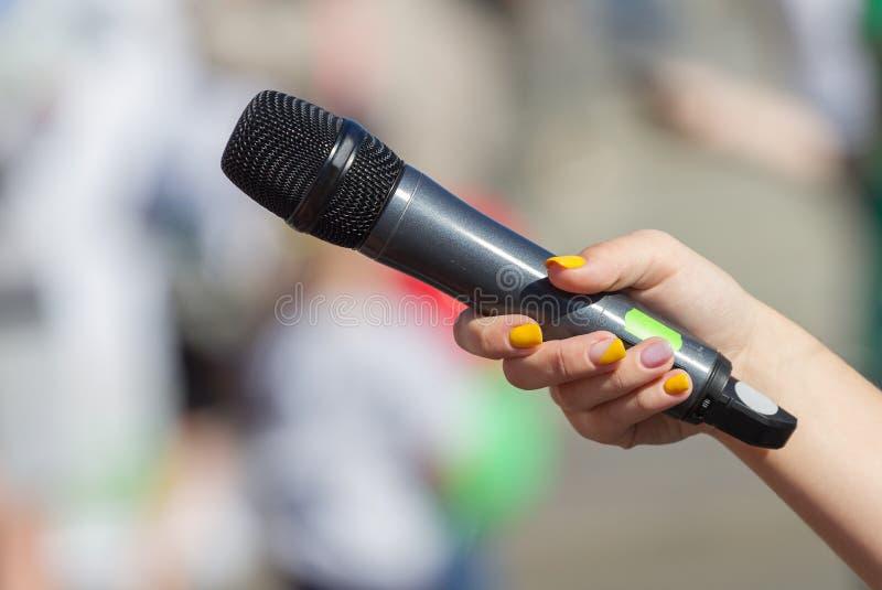 Женская рука держит микрофон стоковое изображение rf