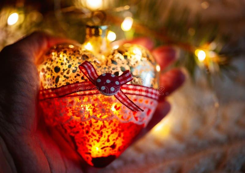 Женская рука держит стеклянное сердце, игрушку рождества - гирлянду в руках на предпосылке теплого связанного свитера Вечер tim стоковые фото
