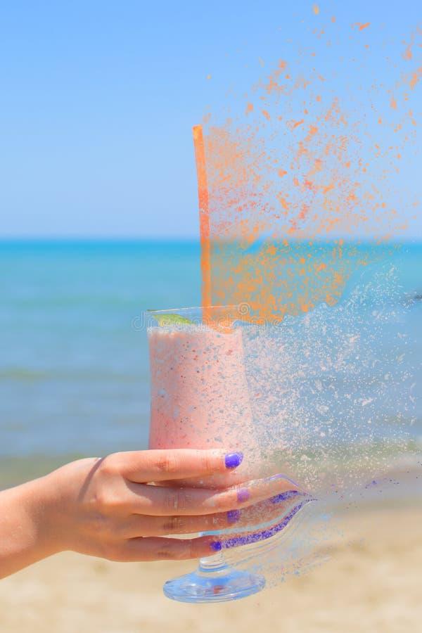 Женская рука держит milkshakes клубники на предпосылке моря с влиянием спада стоковая фотография