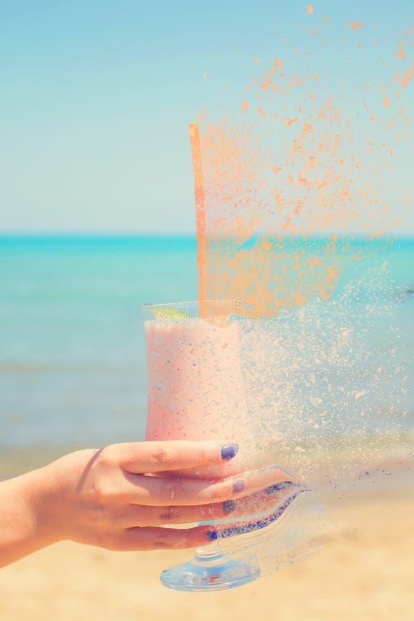 Женская рука держит milkshakes клубники на предпосылке моря с влиянием спада стоковое фото rf