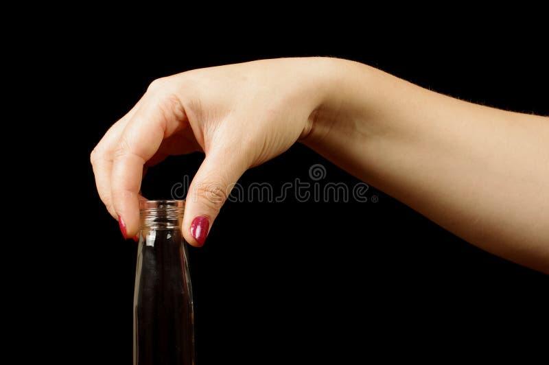 Женская рука держа бутылку водочки стоковое фото rf