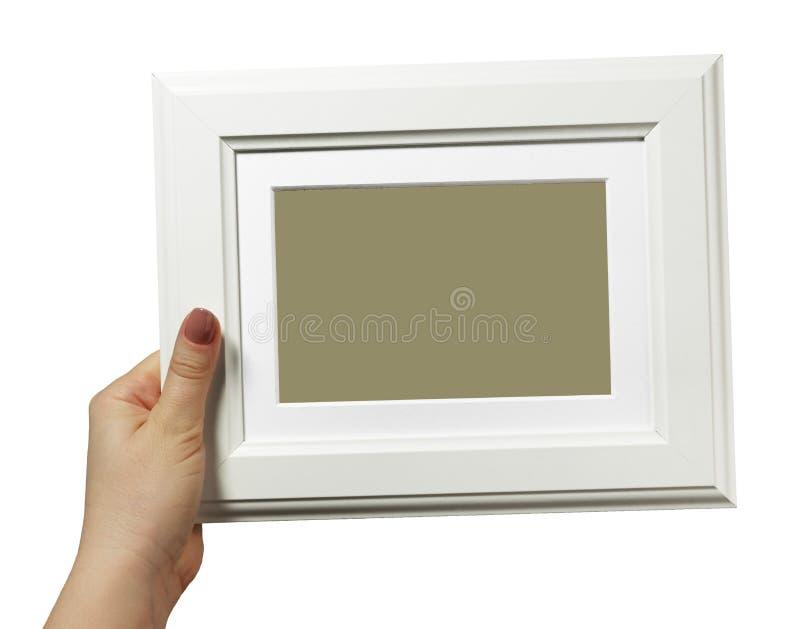 Женская рука держа деревянную рамку изолированный на белой предпосылке стоковые фото
