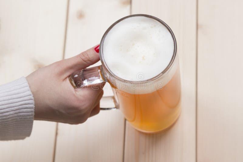 Женская рука держа кружку пива проекта стоковые фотографии rf