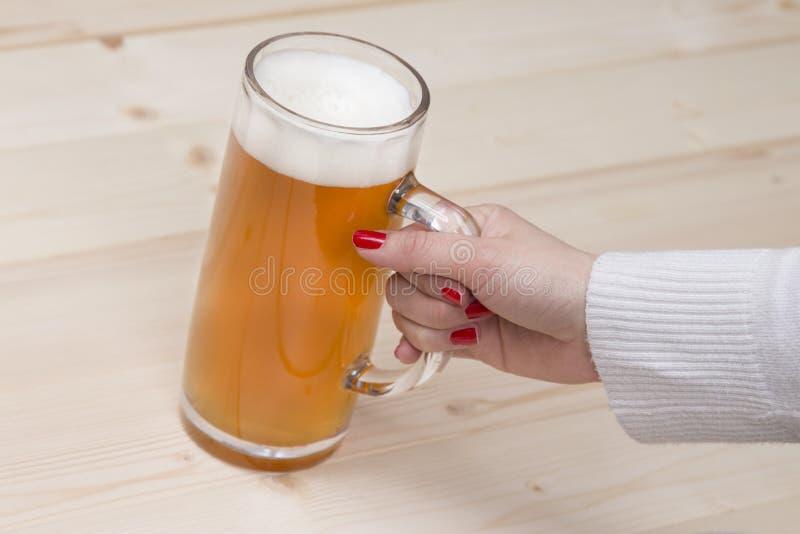 Женская рука держа кружку пива проекта стоковые изображения rf