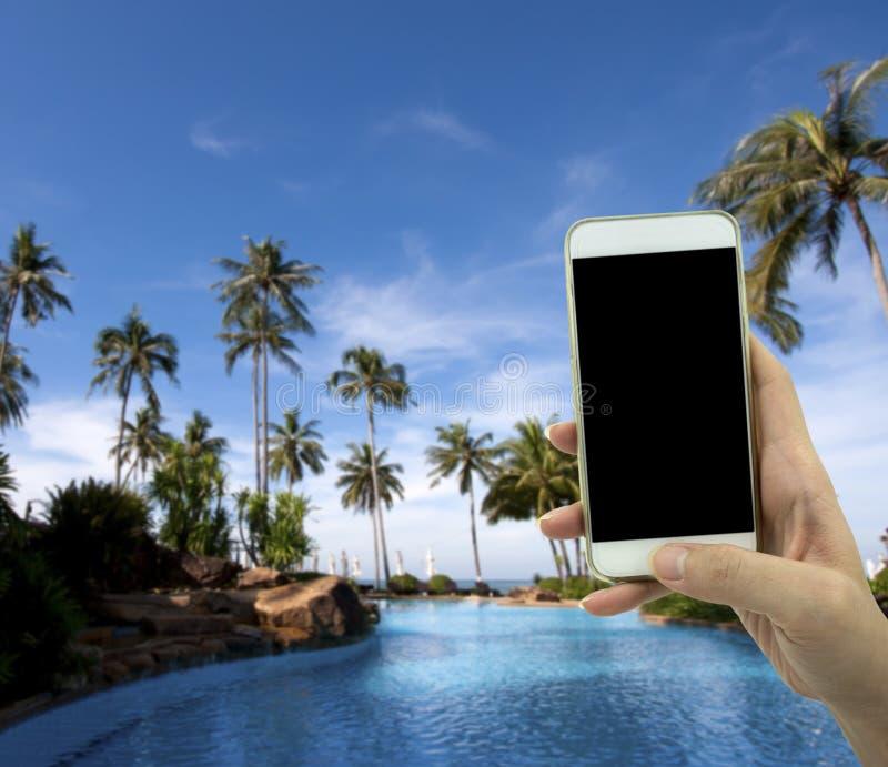 Женская рука держа умный телефон над blured предпосылкой стоковое фото rf