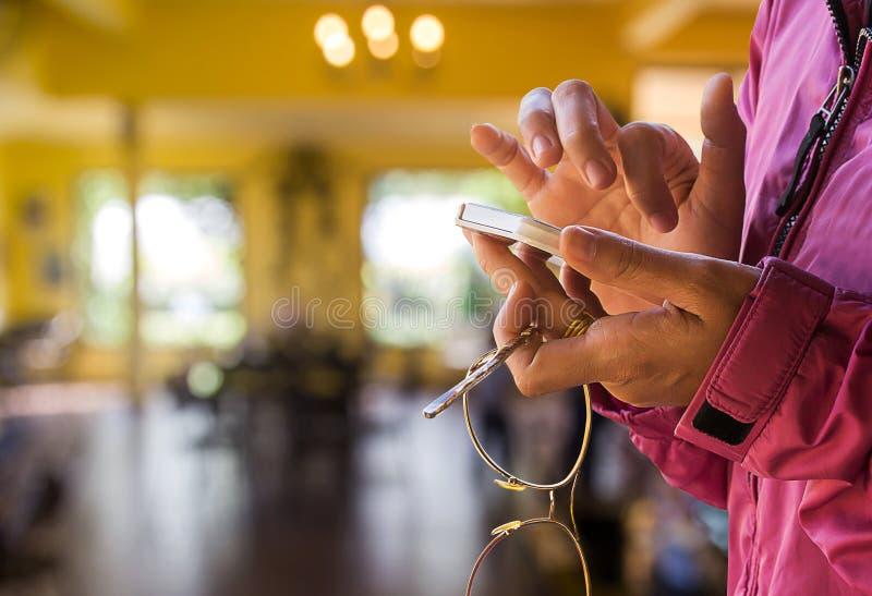 Женская рука держа умный телефон с предпосылкой нерезкости стоковое фото rf