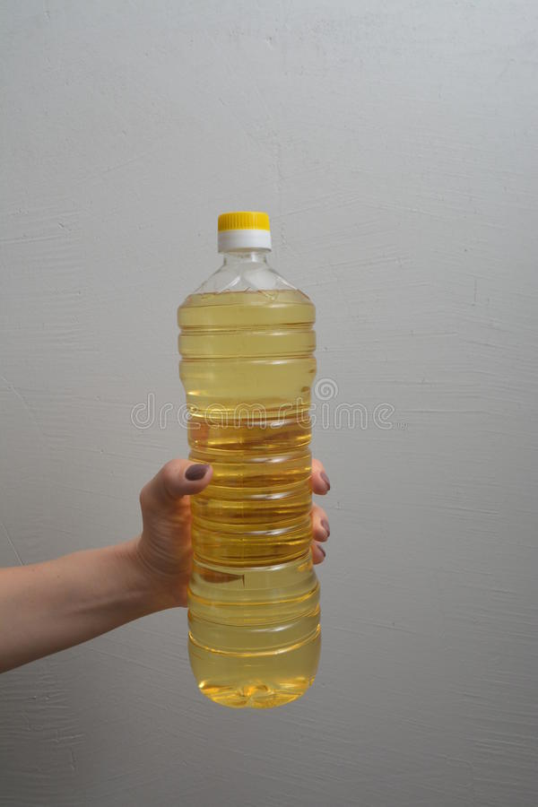 Женская рука держит бутылку масла завода стоковые изображения rf