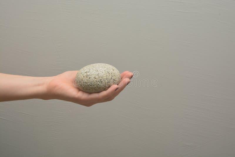 Женская рука держит камень камешка грубый стоковая фотография rf