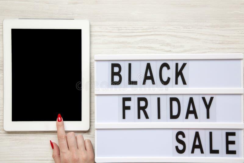 Женская рука используя таблетку, слово ` продажи пятницы ` черное на lightbox над белой деревянной предпосылкой, взгляд сверху Св стоковое изображение