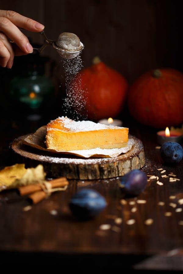 Женская рука лить часть чизкейка тыквы с сахаром замороженности, тыквами, настольной лампой на темной деревянной предпосылке стоковое фото rf