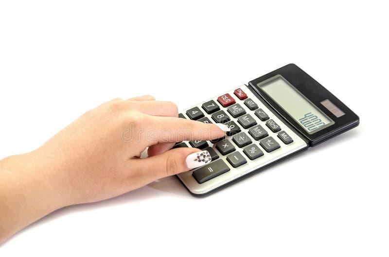 Женская рука печатает что-то на калькуляторе на белой предпосылке стоковое фото
