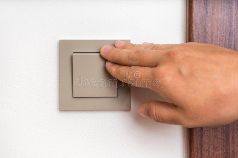 Женская рука поворачивает включено-выключено внутренний выключатель стоковые изображения rf
