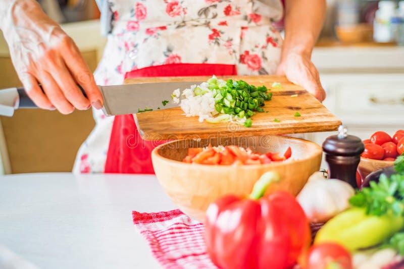 Женская рука положила прерванный зеленый лук-порей в деревянный шар с салатом в кухне Варить овощи стоковые изображения rf