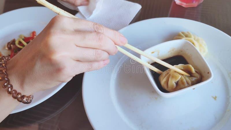Женская рука принимает китайские вареники с палочками и окунает ее в соевом соусе стоковая фотография