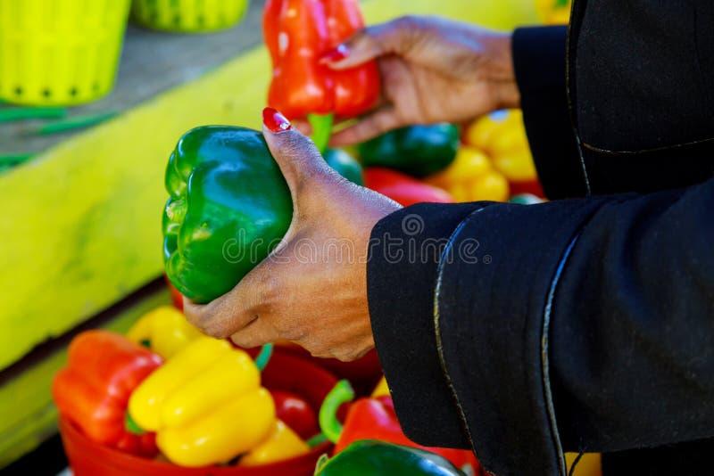 Женская рука принимает свежие овощи в конце-вверх супермаркета женщина выбирая желтые и красные перцы в магазине стоковая фотография